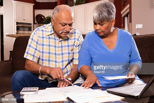 Senior couple paying monthly bills at home.