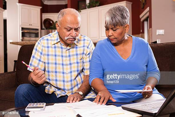 senior couple paying monthly bills at home. - middle class stock pictures, royalty-free photos & images