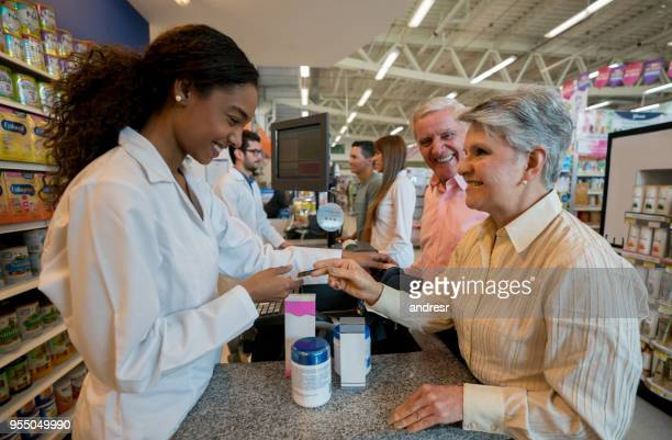 senior couple paying products at the pharmacy checkout with credit card looking very happy - african american man helping elderly stock pictures, royalty-free photos & images