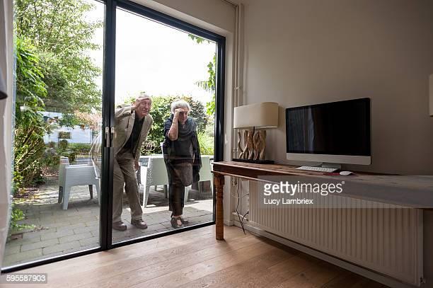 Senior couple peeking inside a modern home