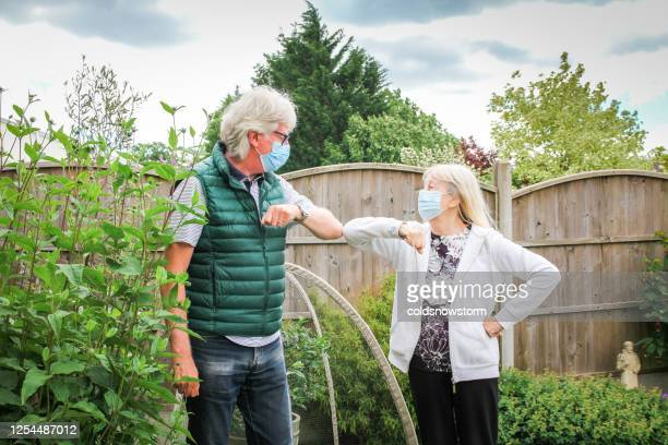 senior couple performing covid-19 elbow bump in garden - social distancing stock pictures, royalty-free photos & images