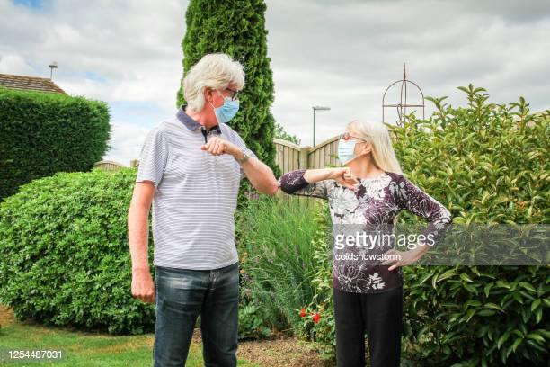 senior couple performing covid-19 elbow bump in garden - state of emergency stock pictures, royalty-free photos & images