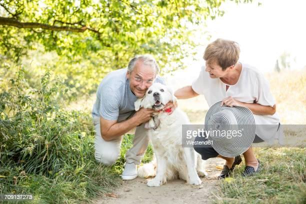 Senior couple petting dog outdoors