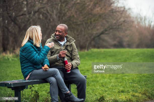 senior couple picnic in their public park - park bench stock pictures, royalty-free photos & images