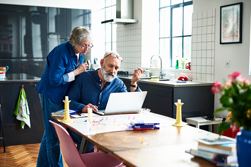 Senior couple planing vacation with map and laptop on table - gettyimageskorea