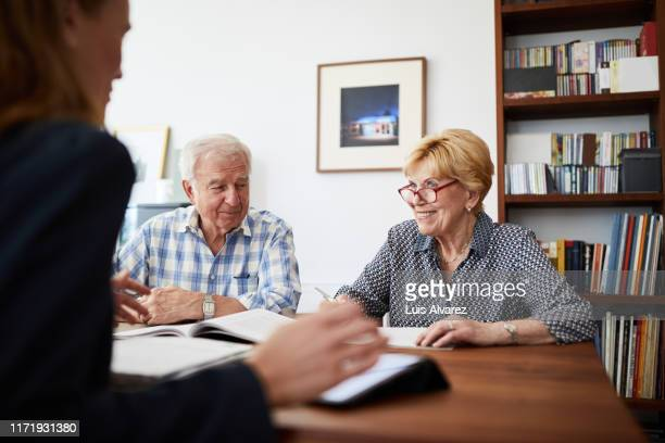 senior couple planning their investments with financial advisor - german short haired pointer stock pictures, royalty-free photos & images