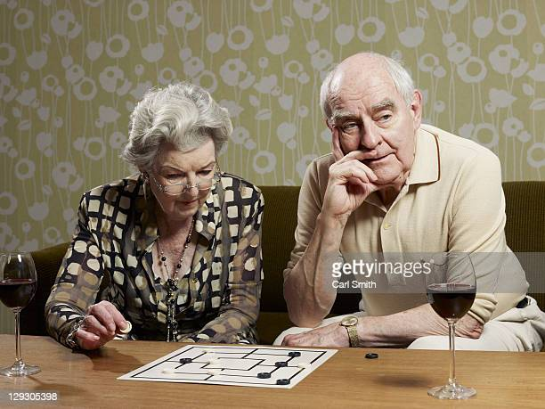 Senior couple play muehle and man looks impatient