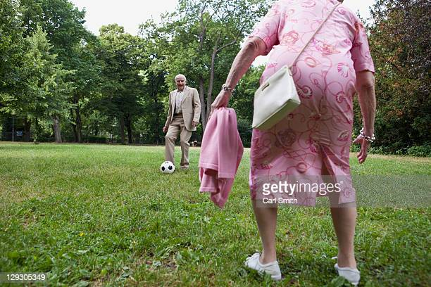 Senior couple play soccer in the park