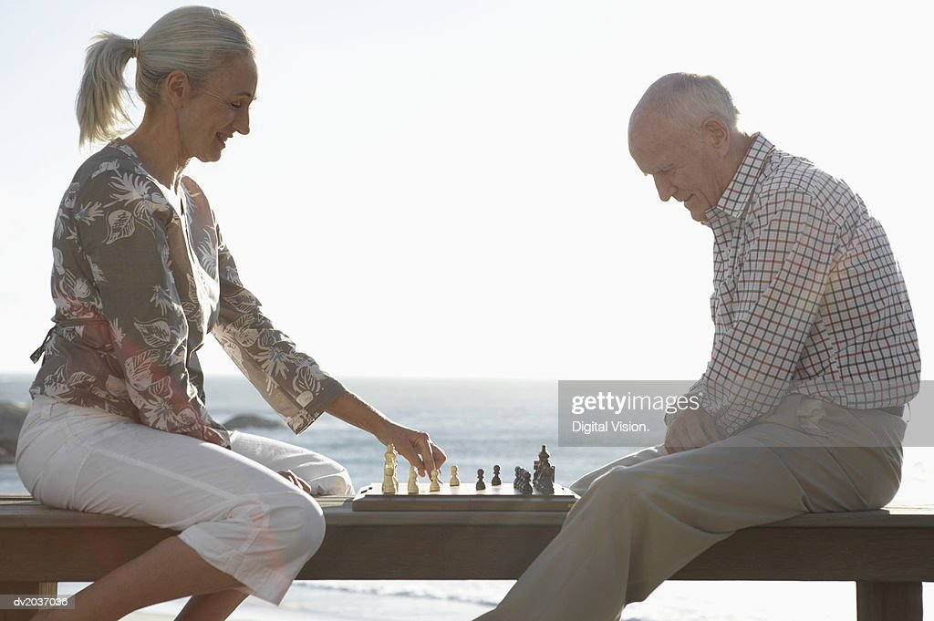 Senior Couple Playing a Game of Chess by the Sea : Stock Photo