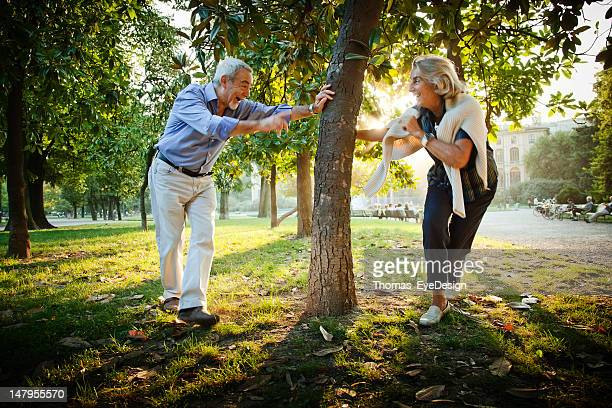 senior couple playing a game of tag. - tag game stock photos and pictures