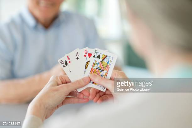 senior couple playing cards - hand of cards stock photos and pictures