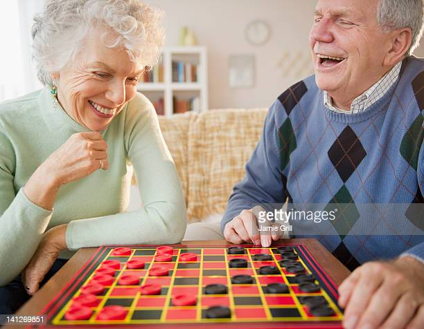 senior couple playing checkers together - chequers stock pictures, royalty-free photos & images