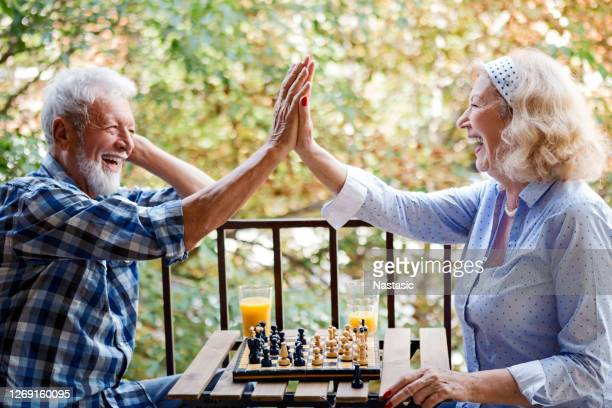 senior couple playing chess at home on a terrace - chess stock pictures, royalty-free photos & images