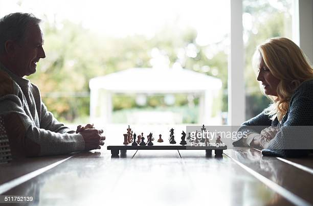 Senior couple playing chess at table
