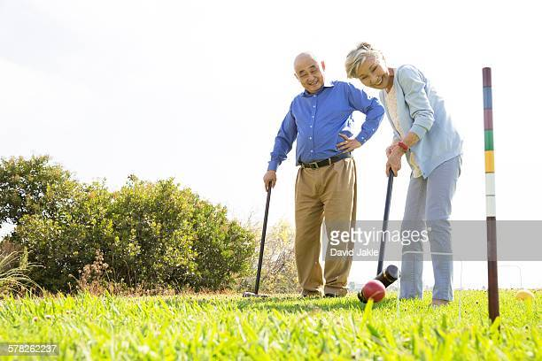 Senior couple playing croquet in park