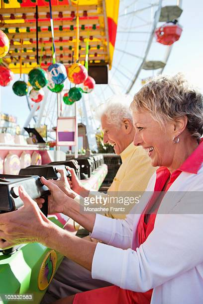 Senior couple playing game at amusement park