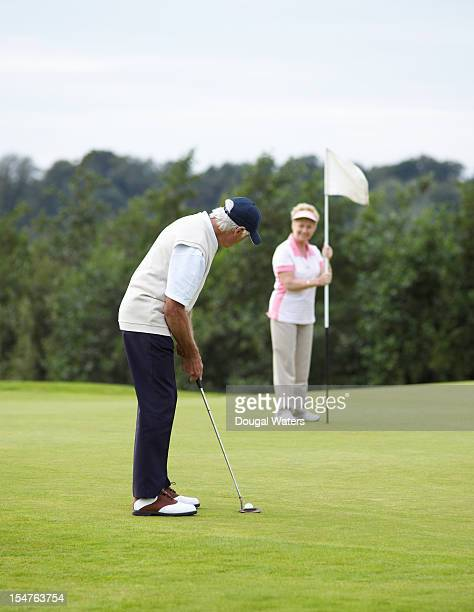 senior couple playing golf. - einlochen golf stock-fotos und bilder
