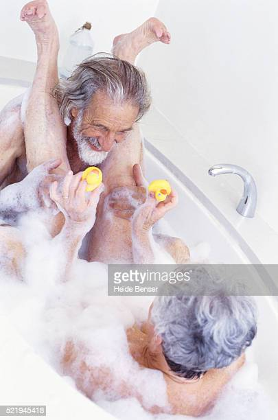 Senior couple playing in bubble bath