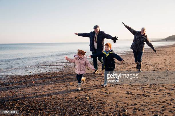 senior couple playing on the beach with their grandchildren - tyne and wear stock pictures, royalty-free photos & images