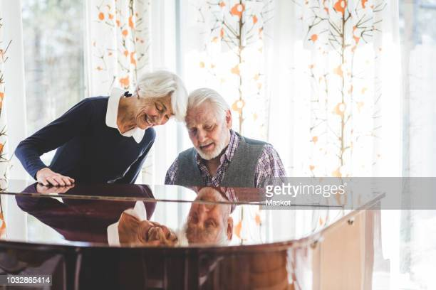 senior couple playing piano together in nursing home - musical equipment stock pictures, royalty-free photos & images