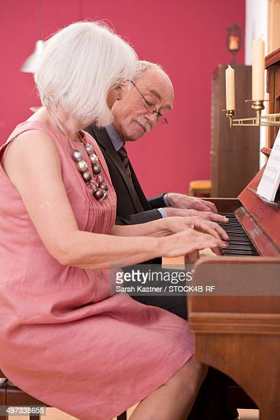 Senior couple playing piano together