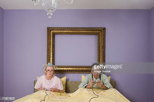 Senior couple playing video game in bed