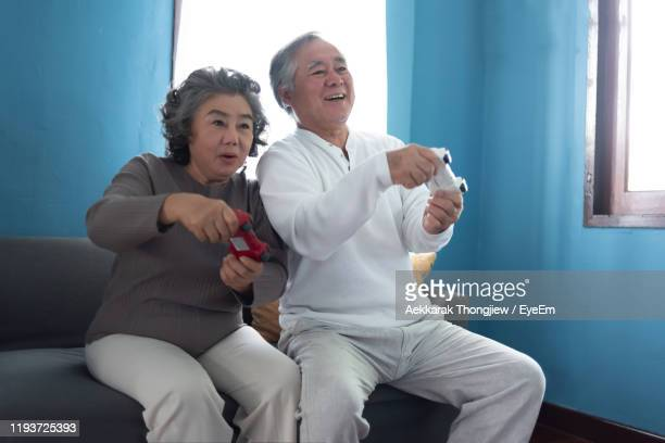 senior couple playing video game while sitting on sofa - disruptaging stock pictures, royalty-free photos & images