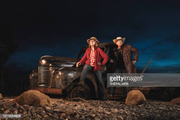 senior couple posing in front of a vintage car - bonnie and clyde stock pictures, royalty-free photos & images