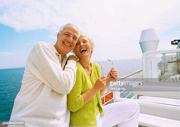 Senior couple posing on boat deck.