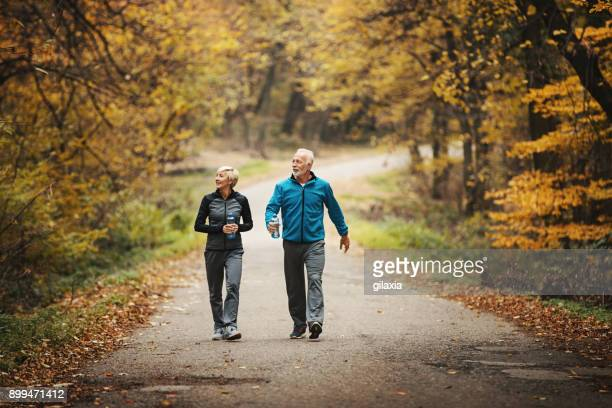 Senior couple power walking in a park.