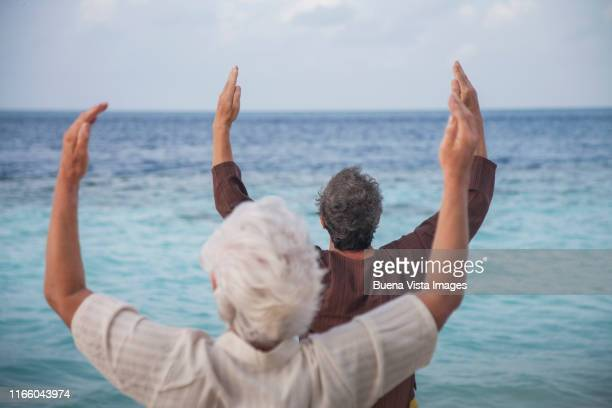 senior couple practicing yoga on the beach - vilamendhoo stock photos and pictures