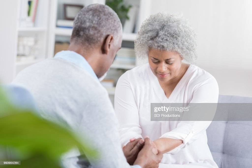 Senior couple pray together at home : Stock Photo