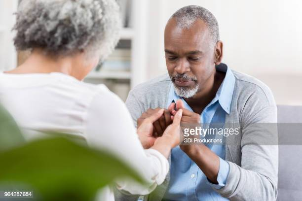 senior couple praying together - praying stock pictures, royalty-free photos & images