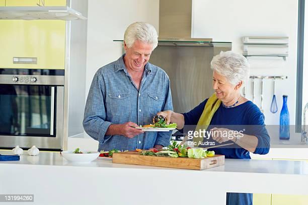 Senior couple preparing food at a domestic kitchen