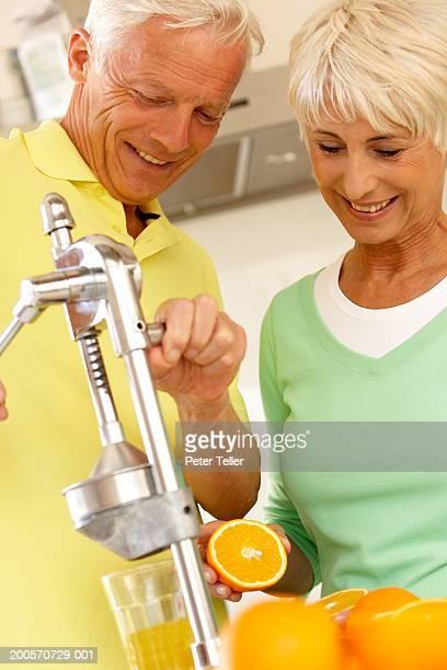 Senior couple preparing fresh orange juice, indoors