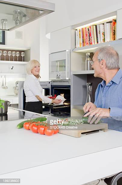 senior couple preparing healthy meal in kitchen - electric stove burner stock pictures, royalty-free photos & images