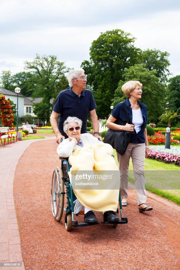 Senior couple pushing wheelchair with old woman : Stock Photo