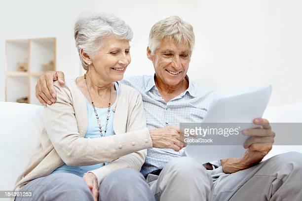 documents de lecture de couple senior - bonne nouvelle photos et images de collection