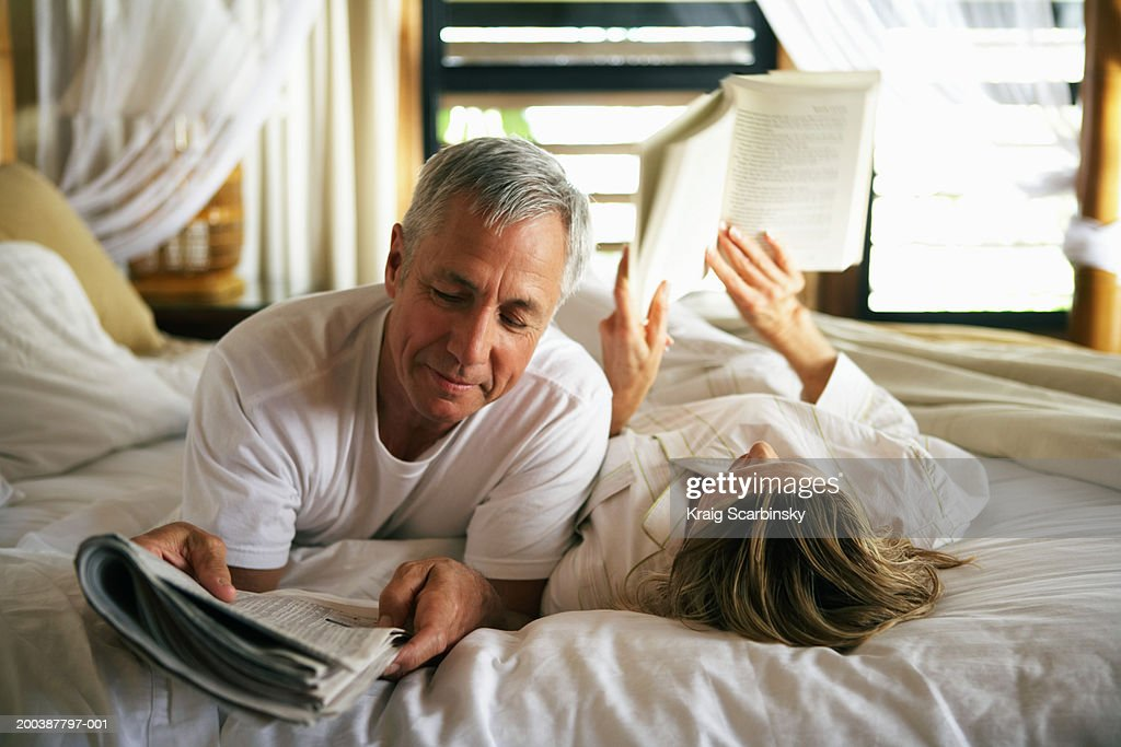 Senior couple reading in bed, close-up : Stock Photo