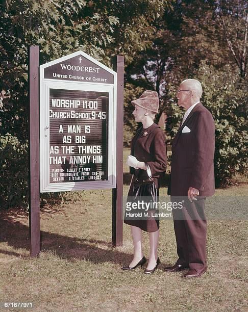 senior couple reading information sign  - escrita ocidental - fotografias e filmes do acervo