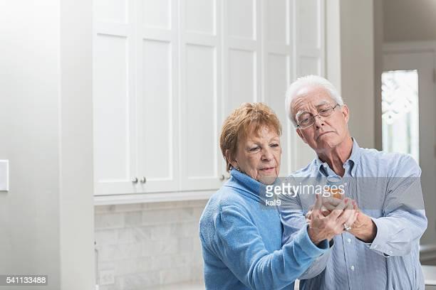 Senior couple reading label on prescription medicine