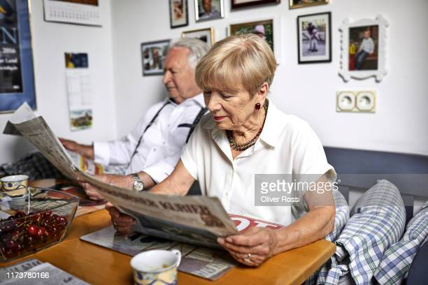 senior couple reading newspaper at home - news not politics stock pictures, royalty-free photos & images