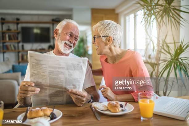 Senior pareja leyendo chistes de diario