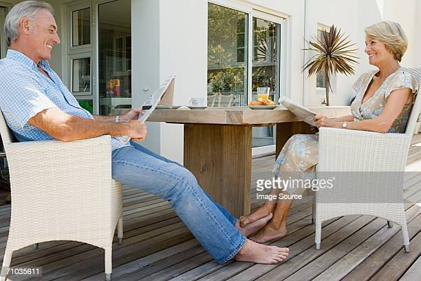 senior couple reading newspapers - playing footsie stock photos and pictures