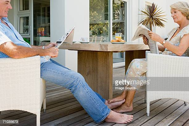 Senior couple reading newspapers