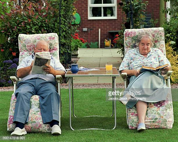 Senior couple reading on adjacent garden chairs