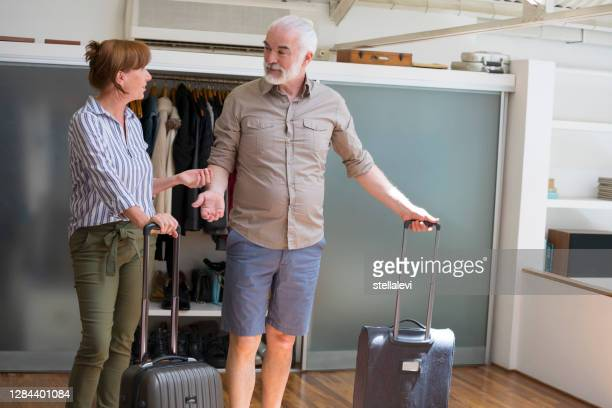 senior couple ready for trip with packed suitcases - stellalevi stock pictures, royalty-free photos & images