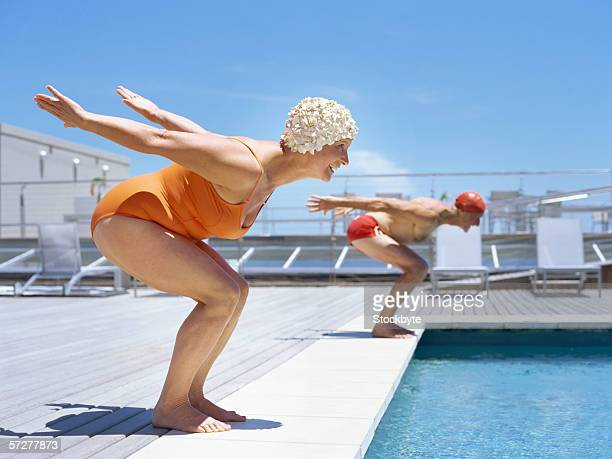 senior couple ready to dive in to swimming pool - active senior woman stock photos and pictures