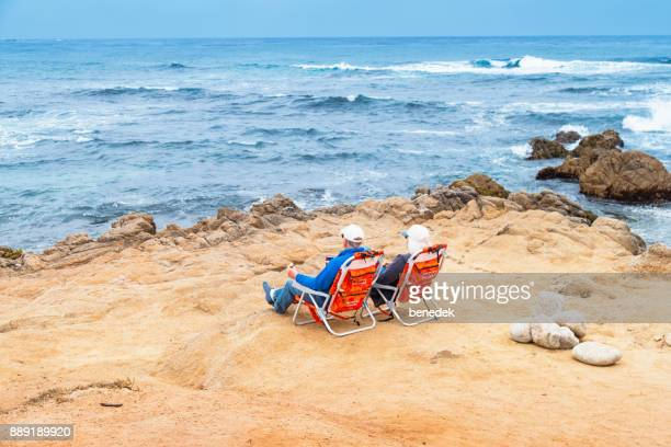 Senior couple relaxes at Asilomar Beach in Monterey California