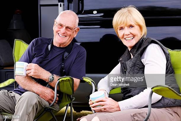 Senior couple relaxing around camper van